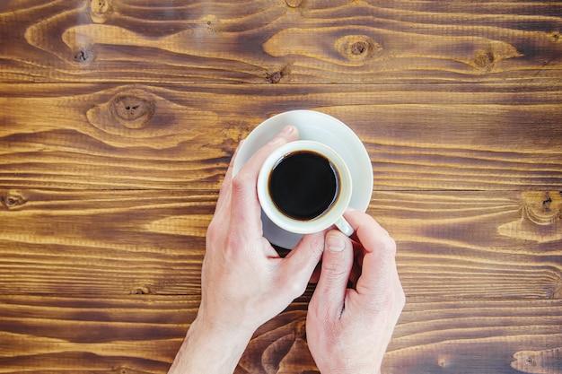 Tazas con un café en manos de hombres y mujeres.