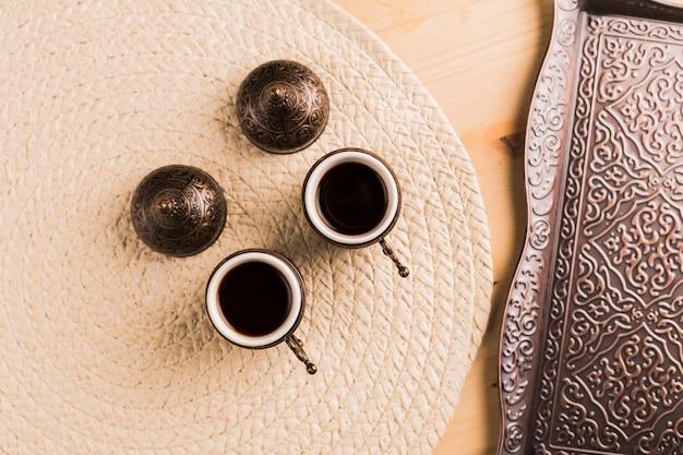 Tazas con café negro y bandeja de metal.