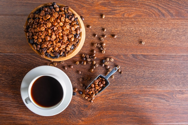 Tazas de café negro y granos de café tostados en una mesa de madera