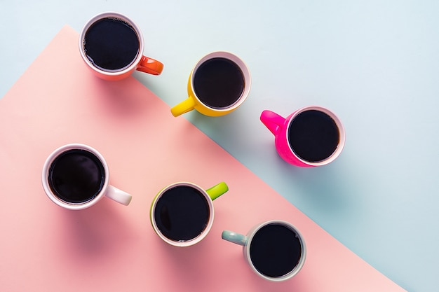 Tazas de café negro sobre fondo de papel azul y rosa