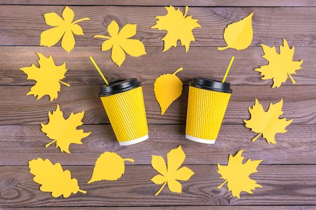 Tazas de café de papel amarillo y hojas de otoño cortadas de papel sobre madera