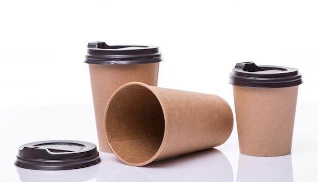 Tazas de café de papel cubierto de diferentes tamaños aislados en blanco