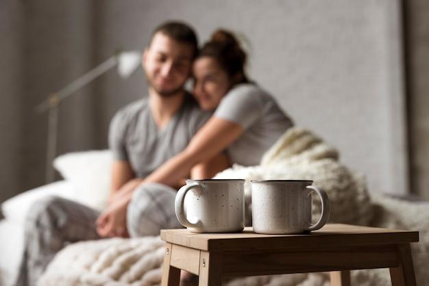 Tazas de café sobre la mesa con la joven pareja detrás