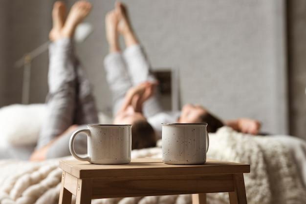 Tazas de café sobre la mesa con pareja detrás en la cama