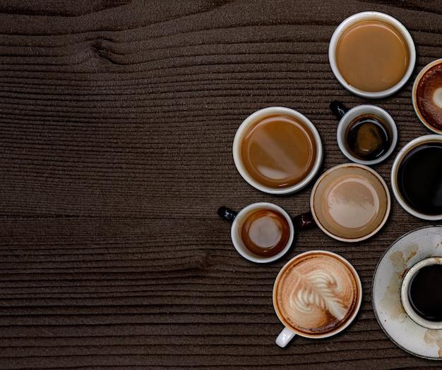 Tazas de café sobre un papel tapiz con textura de madera de color marrón oscuro