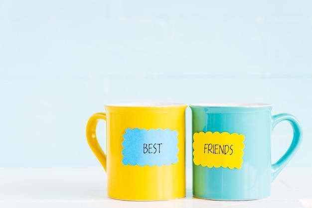 Las tazas de café en la tabla de madera con la etiqueta de papel y los mejores amigos mandan un sms.