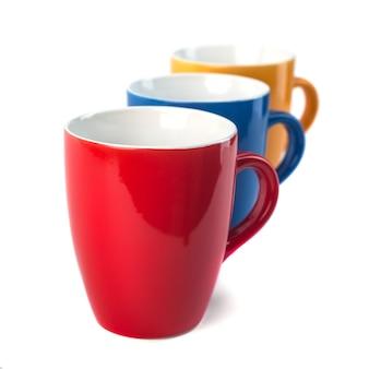 Tazas de cerámica de tres colores sobre un fondo blanco.
