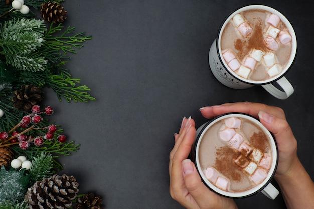 Tazas de chocolate caliente con malvaviscos y decoración navideña, aplanada con ramas de abeto, bebida caliente.