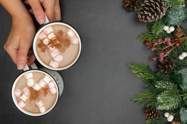 Tazas de chocolate caliente con malvaviscos y decoración navideña, aplanada con ramas de abeto.