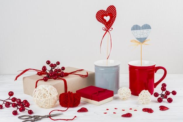 Tazas con corazones en varitas cerca de pequeños corazones, tijeras y regalos.