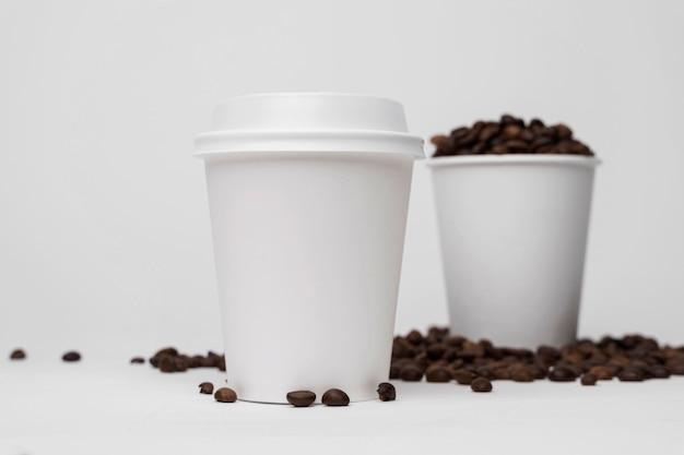 Tazas y granos de café de ángulo bajo