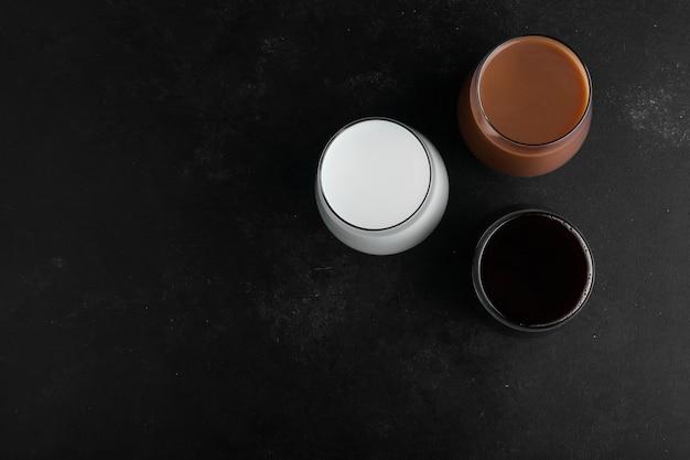 Tazas de leche, chocolate y espresso oscuro sobre superficie negra, vista superior.