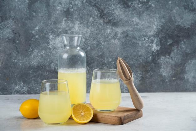 Tazas llenas de limonada con rodaja de limón y exprimidor de madera.