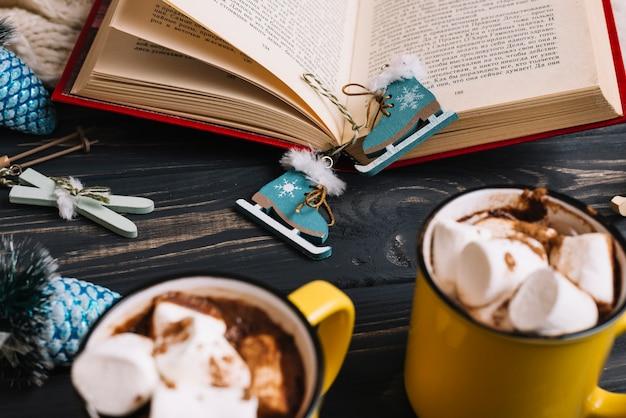 Tazas con malvaviscos y bebidas cerca de decoraciones navideñas y libro.