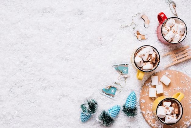 Tazas con malvaviscos y bebidas cerca de los juguetes de navidad en la nieve