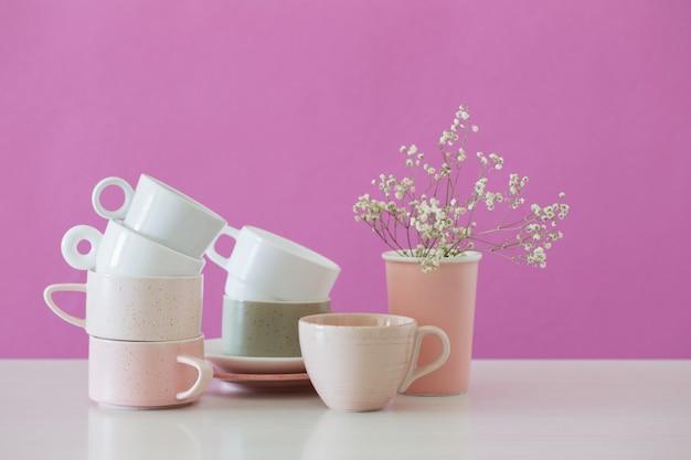 Tazas modernas en mesa blanca