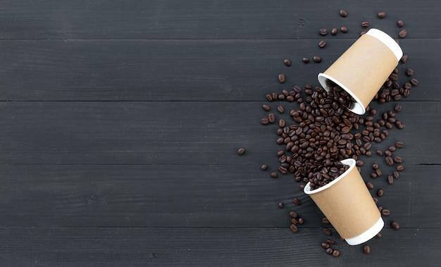 Tazas de papel de café y frijol sobre fondo de madera negra. vista superior