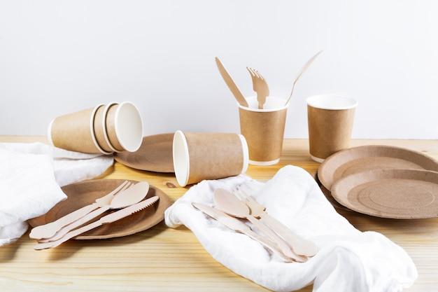 Tazas de papel marrón, platos, cubiertos de madera, servilletas de lino sobre fondo de madera