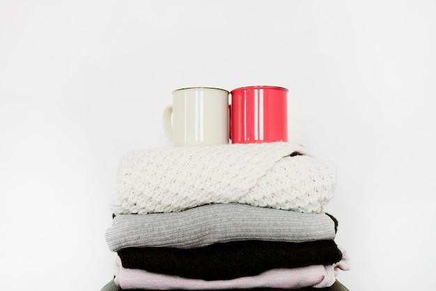 Tazas en la pila de ropa de abrigo