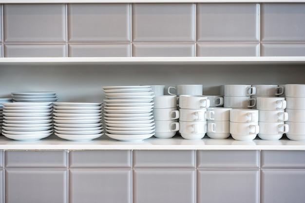 Tazas y platillos de cerámica blanca en los estantes de los restaurantes