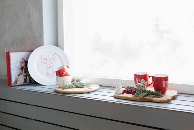 Tazas rojas con té en el alféizar de la ventana, decoración acogedora de navidad