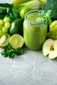 Tazas de tarro de vidrio con batido de salud verde, hojas de col rizada, lima, manzana, kiwi, uvas, plátano, aguacate, lechuga.