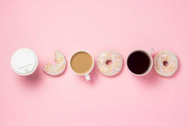 Tazas y taza de papel con café o té, donuts dulces sabrosos frescos expuestos en línea sobre un fondo rosa. concepto de comida rápida, panadería, desayuno, dulces, cafetería. lay flat, vista superior, espacio de copia.