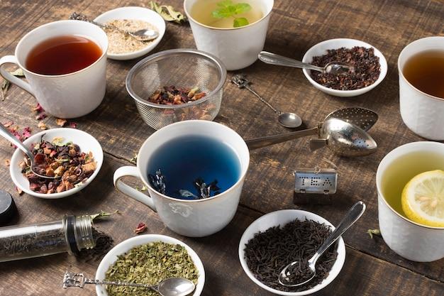 Tazas de té blanco herbario y hierbas en el escritorio de madera