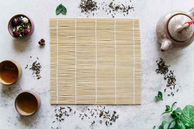Tazas de té de cerámica tradicionales; tetera; flor seca y hojas secas alrededor del mantel individual