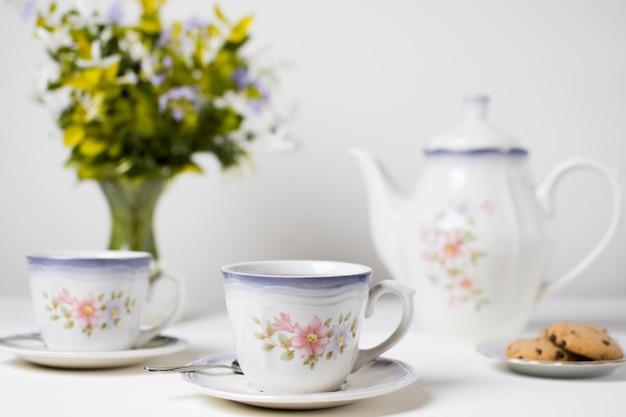 Tazas de té y galletas de cerámica en mesa blanca