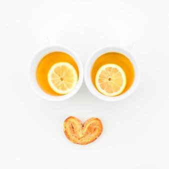 Tazas de té de limón con pastelería palmiers sobre fondo blanco
