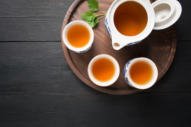 Tazas de té con melissa y hervidor de agua sobre fondo oscuro. concepto de té chino vista desde arriba.