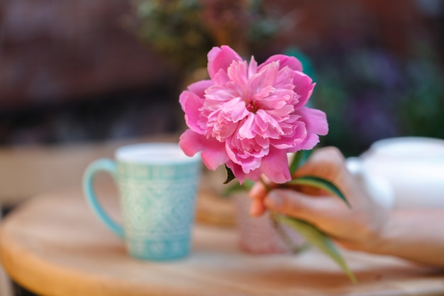Tazas de té y peonía en mesa de madera en street cafe