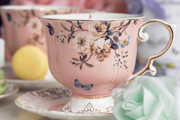 Tazas de té rosa con adornos florales y dulces de macarrón
