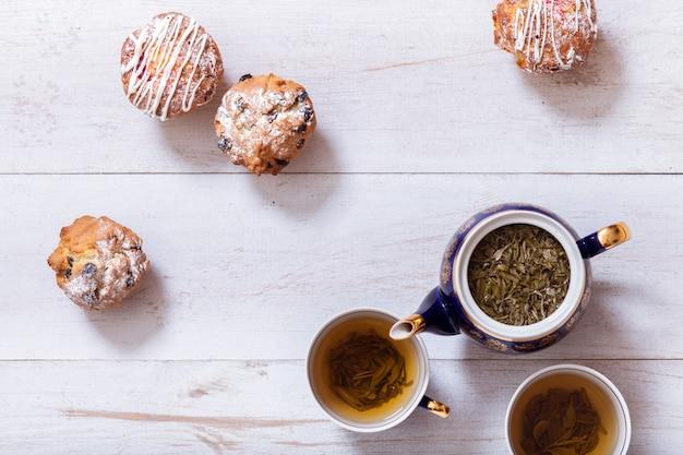 Tazas de té, tetera y magdalenas pasteles en mesa de madera blanca, vista superior