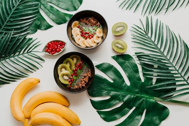 Tazón de acai con bayas saludables, kiwi, aguacate en hojas de palmeras tropicales. comida vegetariana saludable.