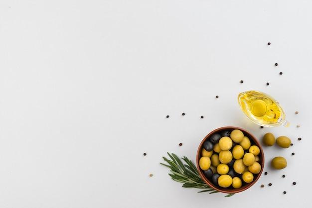 Tazón con aceitunas y taza con aceitunas de aceite en la mesa