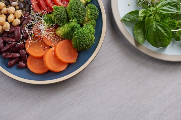 Tazón de almuerzo vegano saludable, ensalada de tazón de buda con ingredientes. garbanzos, diversos frutos secos y tomates, brócoli, zanahorias.