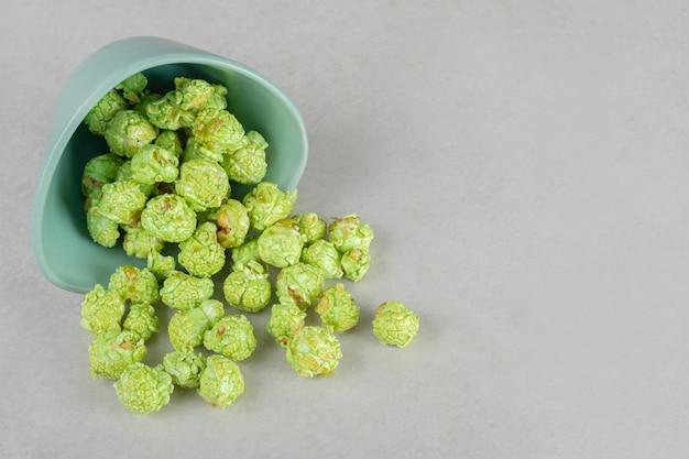 Tazón de aperitivo caído, derramando palomitas de maíz confitadas verdes sobre la mesa de mármol.