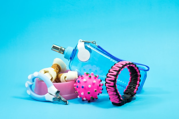 Tazón con aperitivos, collares, juguetes, tijeras de uñas y botellas de agua sobre fondo azul