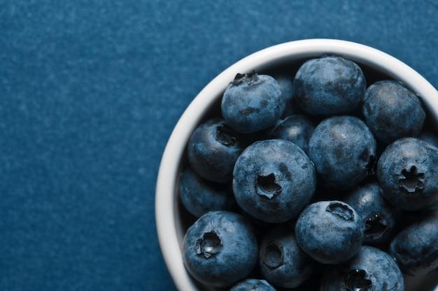 Tazón de arándanos en mesa azul, vista superior