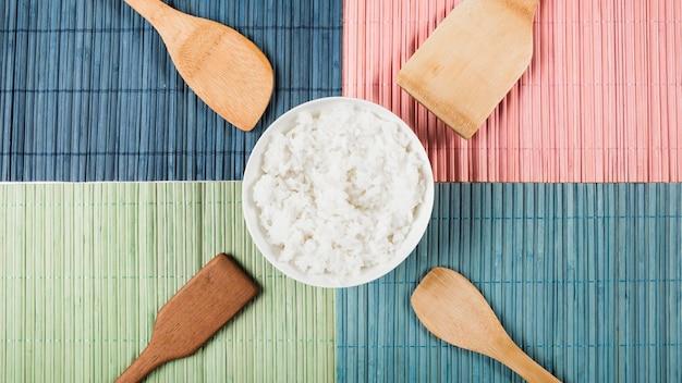 Tazón de arroz al vapor con diferentes tipos de espátula en mantel colorido