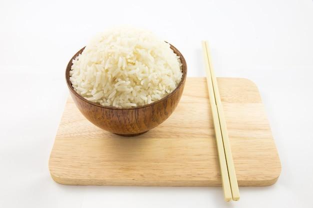 Tazón de arroz y palillos en madera aislados en blanco