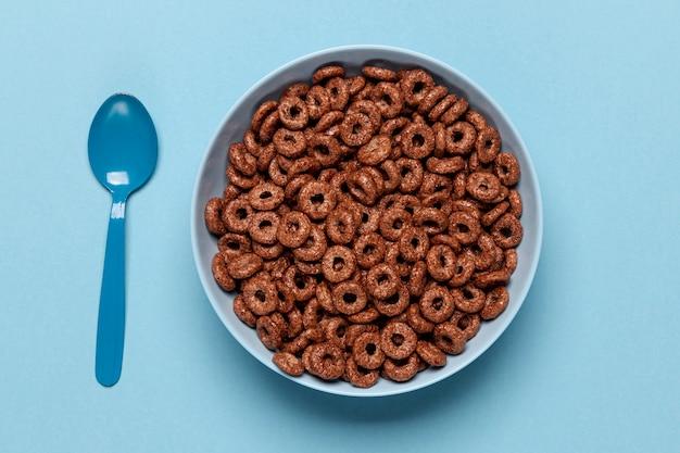 Tazón azul de primer plano de alta vista con cereales de lazo de fruta