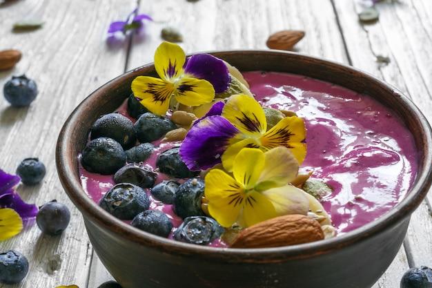 Tazón de batido de arándanos cubierto con bayas frescas, plátano, semillas de chía y flores para un desayuno de dieta vegetariana saludable.