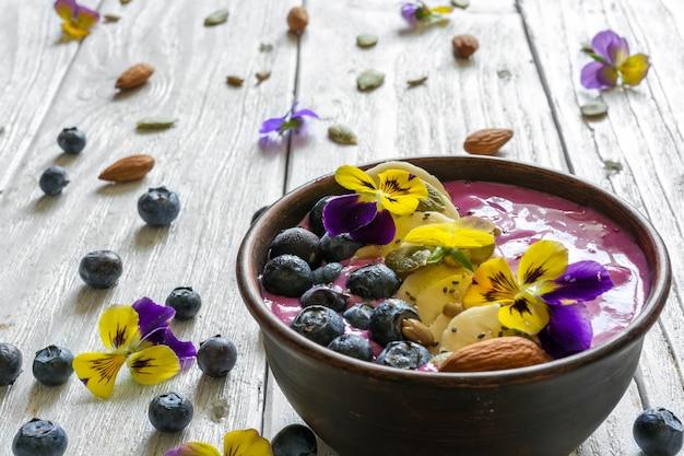 Tazón de batido cubierto con bayas frescas, plátano, semillas de chía, nueces y flores para un desayuno saludable de dieta vegetariana.
