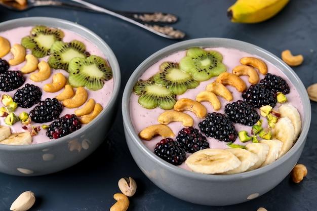 Tazón de batido de desayuno saludable con moras, plátanos, anacardos, kiwi y pistachos en un oscuro