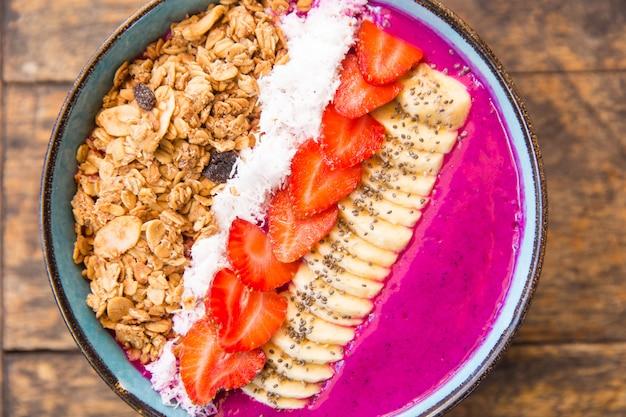 Tazón de batido de fruta de dragón con fresas, granola, semillas de chía y plátano.