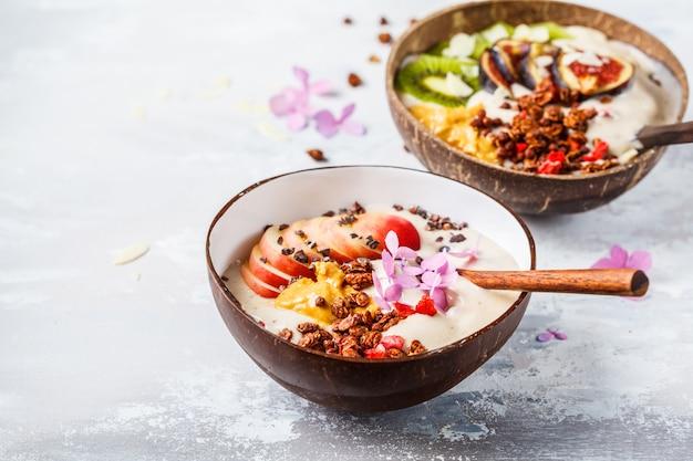 Tazón de batido con frutas y granola con tazón de cáscara de coco sobre fondo gris comida vegana saludable.
