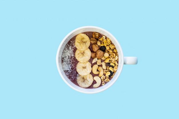 Tazón de batido de frutas con nueces y plátano, vista superior. colocación plana de un tazón de acai con cereales, anacardos y avellanas en superficie azul brillante